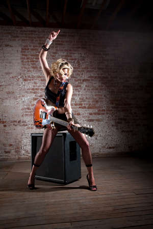 Female punk rock guitarist alone in a warehouse with a large speaker photo