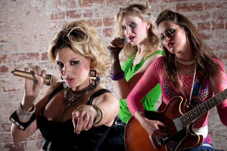 All-girl punk rock band performs in front of a brick background Фото со стока