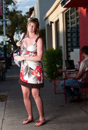 Exhausted pregnant woman with large bag on the sidewalk
