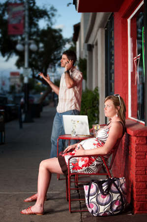 Pregnant woman sitting outside being ignored by partner photo