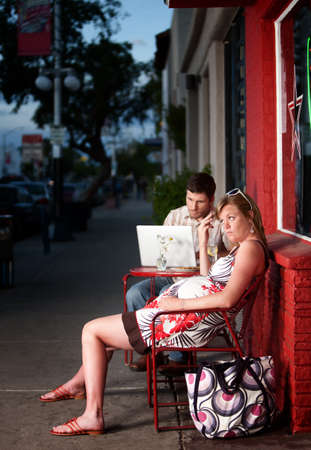 Pregnant woman sitting outside with annoying partner on computer next to her photo