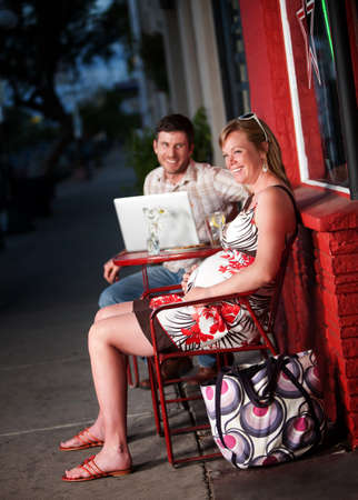 Happy couple sitting outside a cafe with laptop computer photo