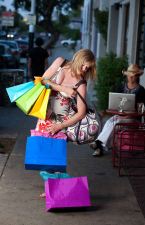 Pregnant woman struggling with multiple shopping bags photo