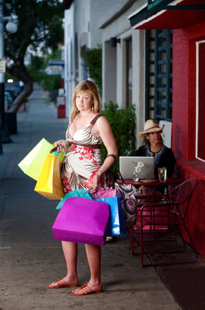 Overwhelmed pregnant woman holding shopping bags outside on sidewalk photo