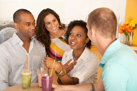 A group of young people are socializing over smoothies.  Horizontal shot. Stock Photo - 7214415