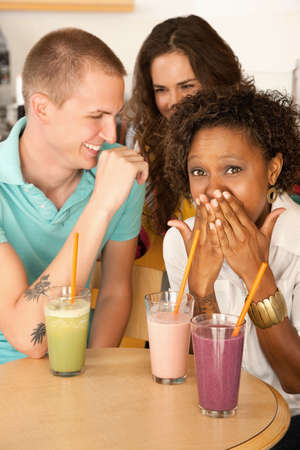 Three people at a cafe drinking frozen beverages. Vertical shot. Stock Photo - 7214477
