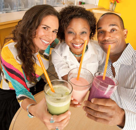 A group of friends are holding smoothies and smiling at the camera.  Square shot. photo