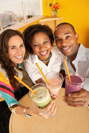 ハイアングルビュー: 冷凍飲料を飲むカフェで 3 人の高角度のビュー。垂直方向のショット。 写真素材