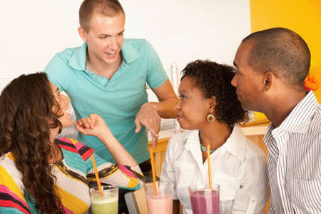 A group of young people are socializing over smoothies.  Horizontal shot. Stock Photo - 7214478