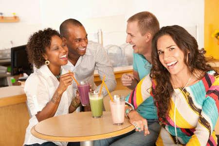 multicultureel: Een groep jonge vrienden zijn socialiseren over smoothies.  Een vrouw is een glimlach op de camera.  Horizont aal schot.