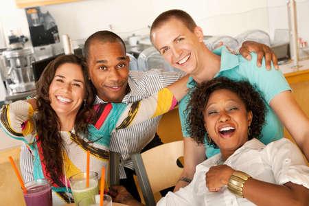 Een groep jonge vrienden lachen samen terwijl het glimlachen naar de camera.  Horizont aal schot.