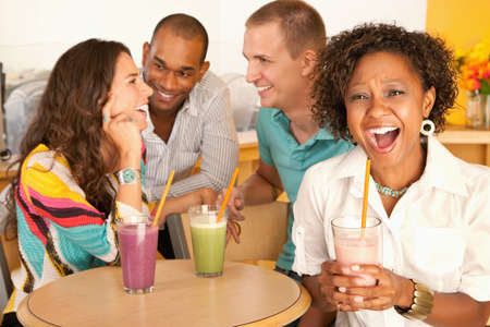 A group of young friends are socializing over smoothies.  One woman is smiling at the camera.  Horizontal shot. photo