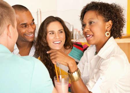 Een groep jonge vrienden genieten van een gesprek over smoothies.  Horizontale schot. Stockfoto
