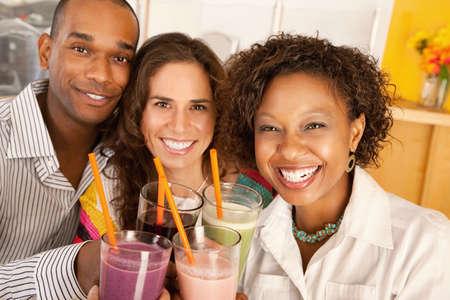 Een groep van vrienden zijn bedrijf smoothies en glimlachen naar de camera.  Horizont aal schot. Stockfoto