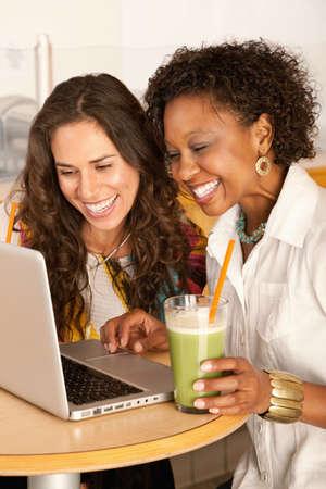 Twee vrouwen werken op een laptop terwijl u geniet van smoothies.  Verticaal schot. Stockfoto