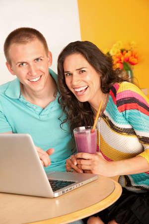 Young couple smile towards the camera while seated at a laptop.  The woman is holding a smoothie in her hand.  Horizontal shot. Stock Photo - 7214490