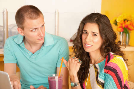 spat: A woman is pointing to a man and making a disgusted face.  Horizontal shot.