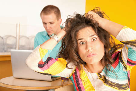 uninterested: Woman pulls at her hair in frustration while her boyfriend works on a laptop in the background.  Horizontal shot. Stock Photo