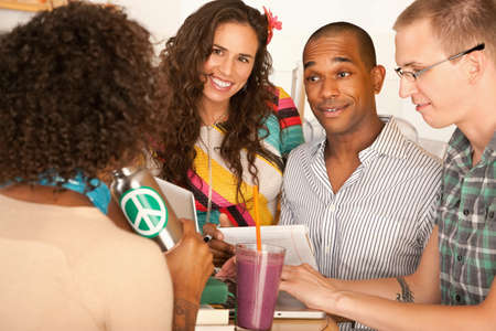 two couples: Two couples at a cafe drinking frozen beverages and using a laptop. Horizontal shot. Stock Photo