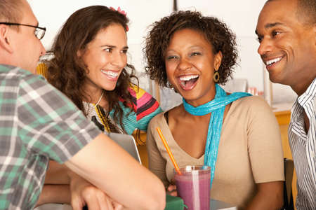 A group of friends are talking and smiling with each other.  One woman is looking towards the camera.  Horizontal shot. Stock Photo