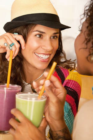 Two women are talking and enjoying smoothies together.  Vertical shot. Stock Photo - 7214468