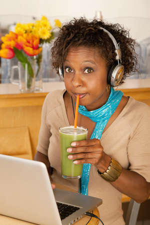 A young woman sitting in a cafe and drinking a frozen beverage. She has a laptop open on the table in front of her and she is wearing headphones draped around her neck. Vertical shot.