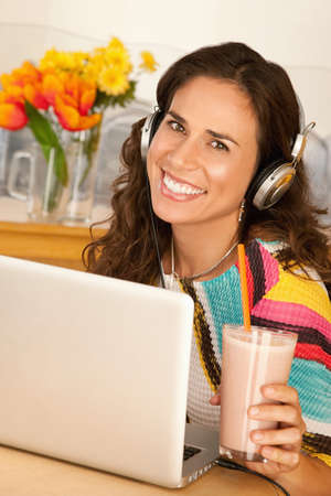 A woman is seated at a desk with a laptop and is drinking a beverage from a cup.  She is wearing headphones and smiling at the camera.  Vertical shot. Stock Photo - 7214437