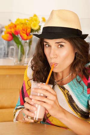 slurp: Una mujer es beber una bebida de una taza y mirando la c�mara. Un disparo vertical.  Foto de archivo