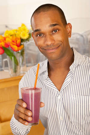 Man is holding a smoothie while smiling at the camera.  Vertical shot. photo