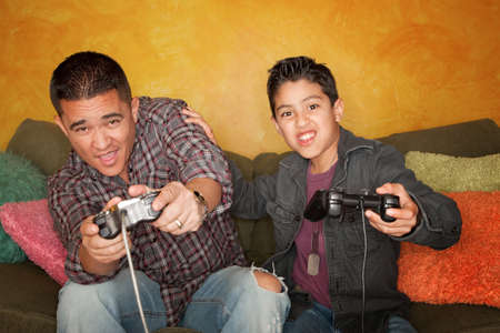 Attractive Hispanic Man and Boy Playing a Video Game with Handheld Controllers