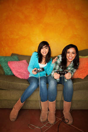 Attractive Hispanic Woman and Girl Playing a Video Game with Handheld Controllers photo