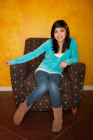 cute braces: Pretty Latina Girl Seated on Colorful Chair Stock Photo