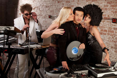 Enviable Asian DJ with admiring female friends photo