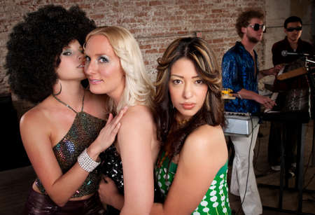 Cute girls embracing at a 1970s Disco Music Party photo