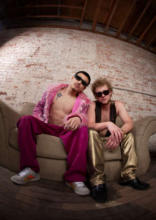 Two cool party goers sitting on a sofa Stock Photo - 7230473