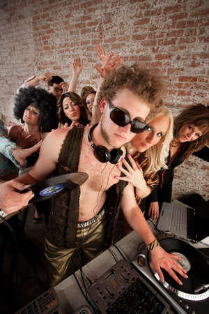 Cool DJ with vest and female admirers photo