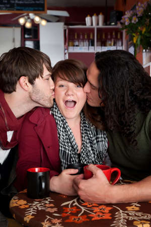 Lucky woman kissed by two handsome men in a cafe photo