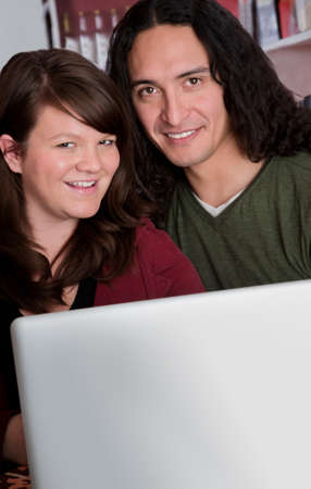 Interracial couple with a laptop at a coffee house with copy space photo
