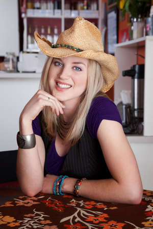 black cowgirl: Smiling blonde woman with cowboy hat in a cafe Stock Photo
