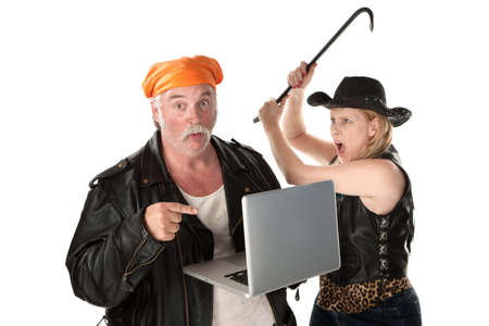 Woman with crowbar threatening man looking at something risque on laptop computer photo
