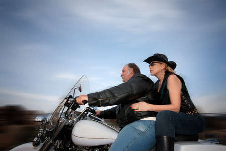 Middle-aged couple riding a motorcycle in the desert
