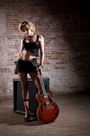 Female punk rocker standing alone with a guitar  photo