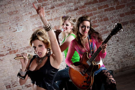 sexy girl dance: All-girl punk rock band performs in front of a brick background Stock Photo