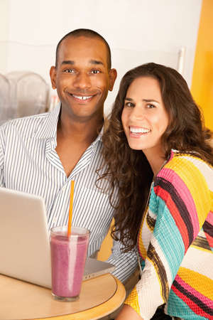 Young couple smile towards the camera while seated at a laptop and smoothie.  Vertical shot. photo