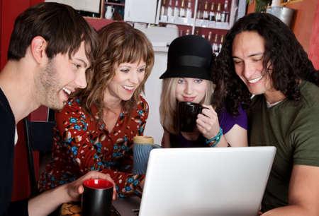 giggle: Cuatro amigos riendo de contenido en un equipo port�til  Foto de archivo