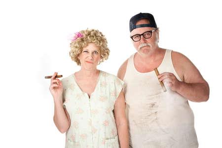Smirking homely couple with cigars on white background photo