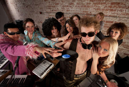 DJ crowded by fans and requests at a party photo