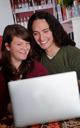Interracial couple with a laptop in a small cafe Stock Photo - 7315872