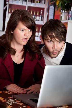 porno: Uomo e donna staring con shock per computer portatile