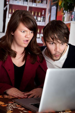 smut: Woman and man staring with shock at laptop computer